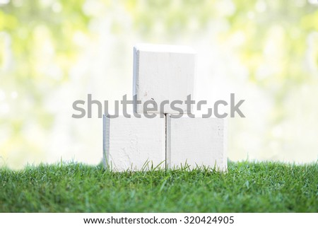 close up still life portrait of wooden blocks on a green grass, ready for your text with bokeh background - stock photo