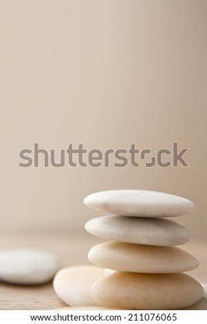 Close up still life side view of a stack of natural white stones piled on top of each other in balance against a plain background. Neutral, calm and relaxing health spa interior colors. - stock photo