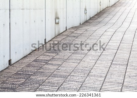 close - up street floor tiles and concrete wall  - stock photo