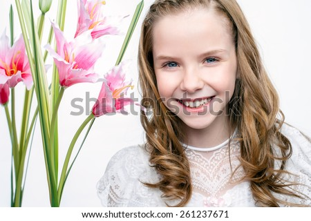 Close up studio beauty portrait of cute communion girl with flowers. - stock photo