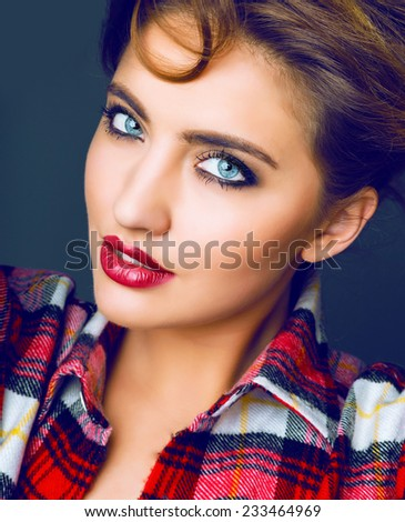 Close up studio fashion portrait of beautiful sensual woman with full berry sexy lips and big blue eyes with smoky make up, wearing red plaid shirt Toned bright colors. - stock photo