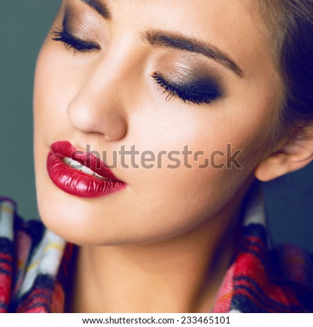 Close up studio fashion portrait of beautiful sensual woman with full berry sexy lips and smoky make up. Toned bright colors. - stock photo
