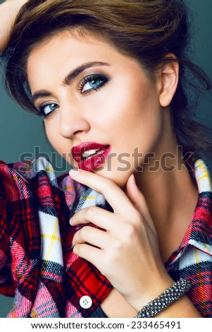 Close up studio fashion portrait of beautiful sensual woman with full berry sexy lips, perfect skin and big blue eyes with smoky make up, wearing red plaid shirt Toned bright colors. - stock photo