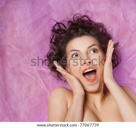 Close-up studio portrait of a beautiful girl with the emotion of delight - stock photo
