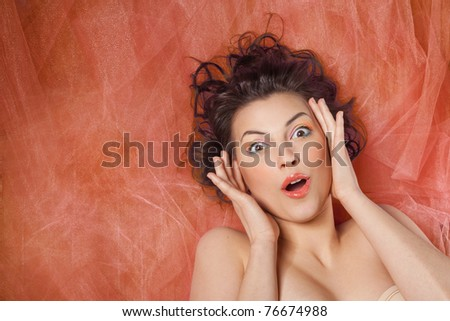 Close-up studio portrait of a beautiful girl with the emotion of surprise - stock photo