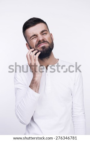 Close-up studio portrait of a grimacing thinking man irritable itchy his beard. Isolated on a light background. - stock photo
