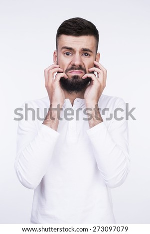 Close-up studio portrait of a man tired of his beard. Isolated on a light background. - stock photo