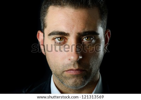 Close up studio portrait of a serious man on black background - stock photo