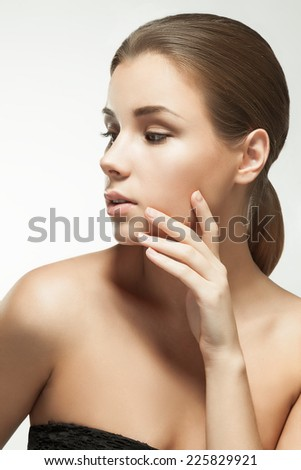 Close up studio portrait of a young European woman with clear healthy perfect skin on a gray background. Beauty model woman face - stock photo