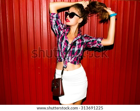 Close up studio portrait of cheerful blonde hipster girl going crazy making funny face and showing her tongue.high fashion portrait of young elegant woman takes her ponytail,black glasses,red lips - stock photo