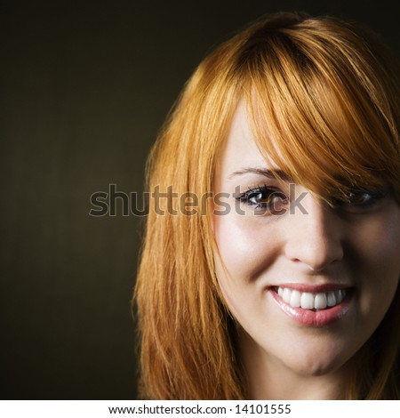Close-up studio portrait of pretty young redheaded female.