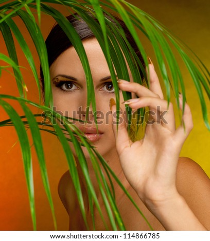 close-up studio portrait of young beautiful tanned woman with long acrylic leopard nails and makeup - stock photo