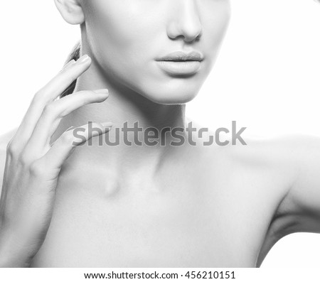 Close-up studio portrait of young caucasian brunette woman with natural lips and make-up  isolated on white. Touch her perfect skin. Studio portrait. Black and white