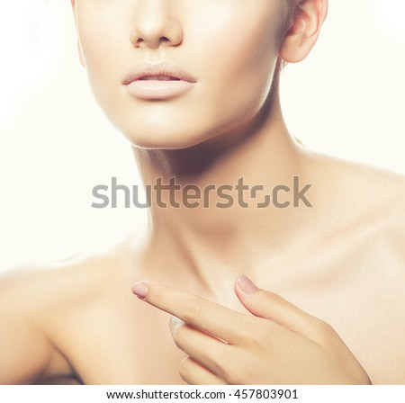 Close-up studio portrait of young caucasian brunette woman with natural lips, make-up and blue eyes isolated on white. Touch her perfect skin. Studio portrait. Toned - stock photo