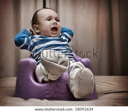 Close up studio shot of a baby boy sitting on a rubber baby support chair on the bed screaming out loud. - stock photo