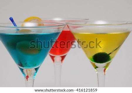 Close-up studio shot of a group of three garnished Martini cocktails (red, blue and yellow) on grey background. - stock photo