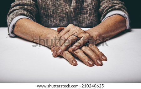 Close-up studio shot of a senior woman's hands resting on grey surface. Old lady sitting with her hands clasped on a table. - stock photo