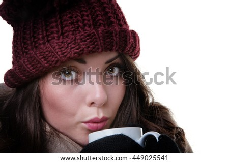 Close up studio shot of a young, pretty model, wearing an woollen winter hat, coat and gloves,whilst holding a mug.  - stock photo