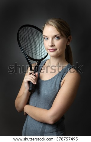 Close up studio shot of a young slim fitness model holding a tennis racket in her right hand, shot on a grey background