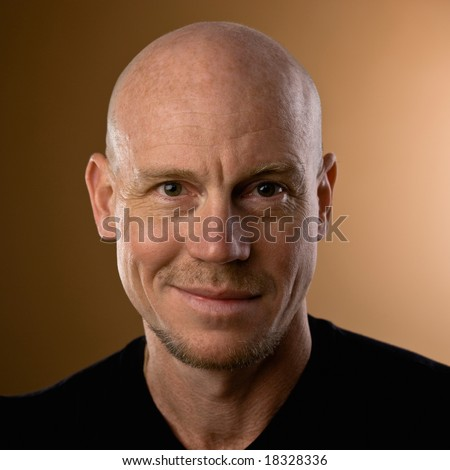 Close up studio shot of bald man with goatee and mustache - stock photo