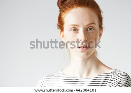 Close up studio shot of beautiful redhead Caucasian young woman with healthy clean skin with freckles, in striped shirt looking at the camera with calm and serious expression. Selective focus - stock photo
