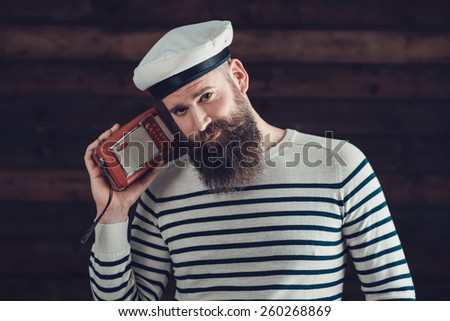 Close up Stylish Handsome Man with Long Beard in Sailor Attire, Holding a Vintage Radio While Looking at the Camera. - stock photo