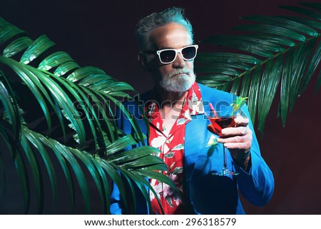 Close up Stylish Middle Aged Businessman with Sunglasses Holding a Cocktail Drink between Indoor Palm Trees During a Tropical Party at Night - stock photo