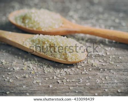 Close up sugar in wood spoon on wood table, Healthy cane sugar on wooden spoon - stock photo