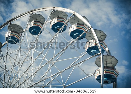 Close up summer carnival ferris wheel against blue sky