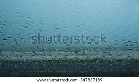 Close up surface of glass and blur background is the sea next from the road.