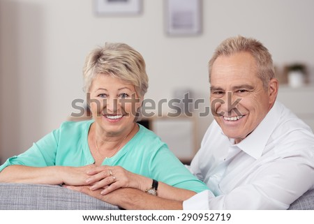 Close up Sweet Happy Matured Couple Sitting at the Living Room Couch, Smiling at the Camera Holding Their Hands. - stock photo