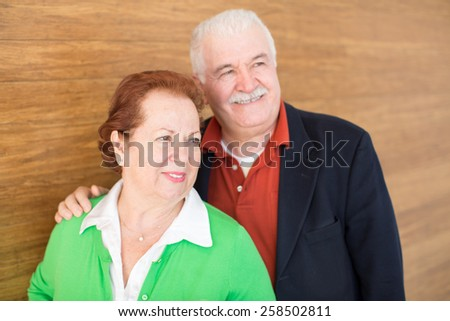 Close up Sweet Happy Retired Couple Posing in Front of a Wooden Wall Background. - stock photo