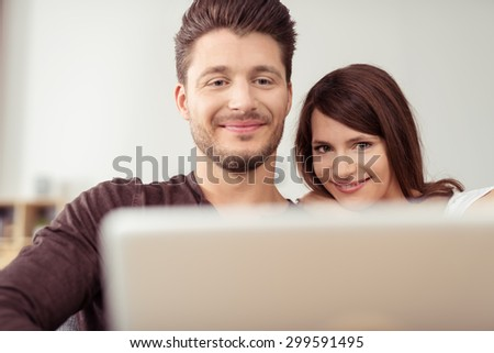 Close up Sweet Young Couple Watching a Movie on Laptop Computer Together with Happy Faces. - stock photo