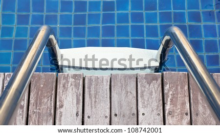 Close up Swimming pool with stair an wood floor - stock photo