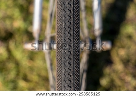 Close up Symmetry Bicycle Tire on Green Grass background