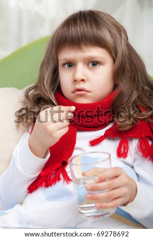 Close-up sympathetic little sick girl wrapped in red scarf under blanket in bed is taking the pill and glass of water - stock photo