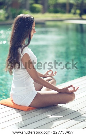 Close up Tan Young Woman with Long Black Hair Doing Yoga at the Poolside to Stay Physically and Mentally Healthy. Captured in Side View. - stock photo