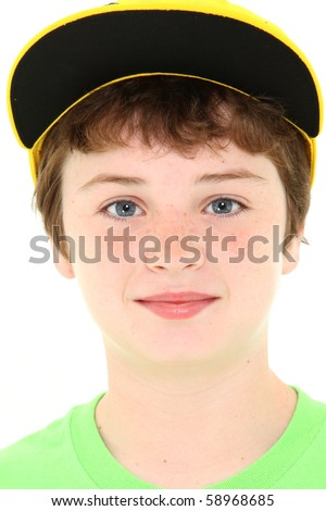 Close up ten year old american boy in yellow cap and green shirt over white.