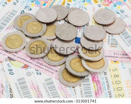 Close up Thai lottery tickets and coins  - stock photo