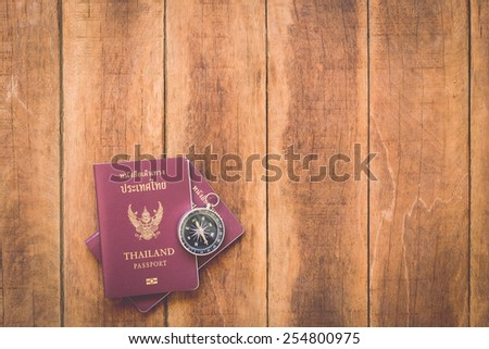 Close up Thailand passport and compass on wood - stock photo