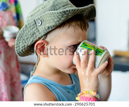 Close up Thirsty Cute White Young Boy with Cowboy Hat, Drinking Water on a Glass Seriously - stock photo