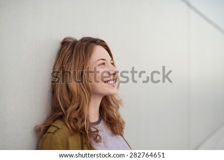 Close up Thoughtful Happy Young Woman Leaning on the Wall While Looking up with a Toothy Smile. - stock photo