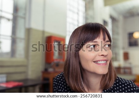 Close up Thoughtful Middle Age Woman Smiling at Far Right While at Inside the Office. - stock photo