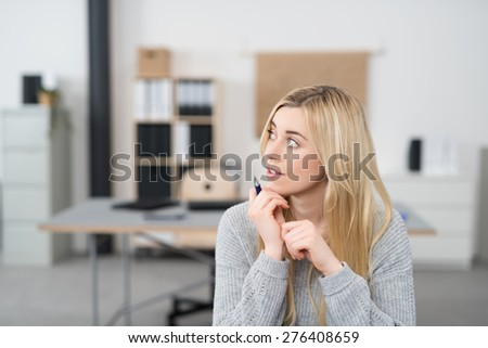Close up Thoughtful Pretty Office Girl with Long Blond Hair Sitting at her Desk While Holding a Pen and Looking to the Upper Left of the Frame Seriously - stock photo