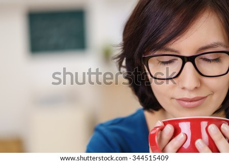 Close up Thoughtful Woman Wearing Eyeglasses Enjoying the Aroma of a Hot Coffee in a Cup. - stock photo