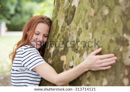 Close up Thoughtful Young Nature-Lover Woman Hugging a Huge Tree Trunk at the Park with Happy Facial Expression. - stock photo