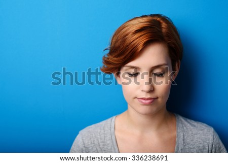 Close up Thoughtful Young Woman Against Blue Wall Background with Copy Space on the Left.