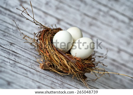 Close up Three White Chicken Eggs in a Nest on a Wooden Table in a Diagonal Shot - stock photo