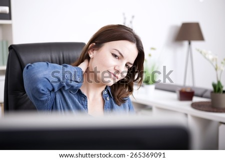 Close up Tired Office Woman Sitting at the Office, Holding the Back of her Neck While Looking at the Computer Monitor. - stock photo