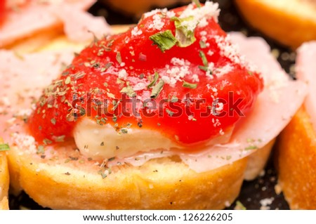Close up to bruschetta with the cheese and ham - stock photo
